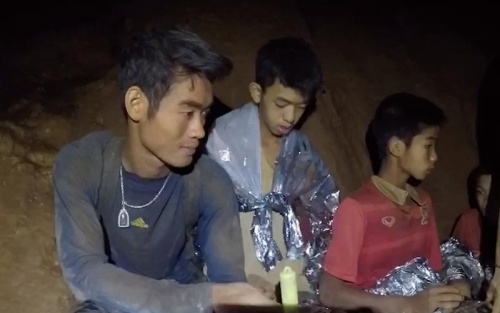 Ekkapol Chantawong (left)  is among the last 3 including 2 boys to be escorted by divers out of flooded